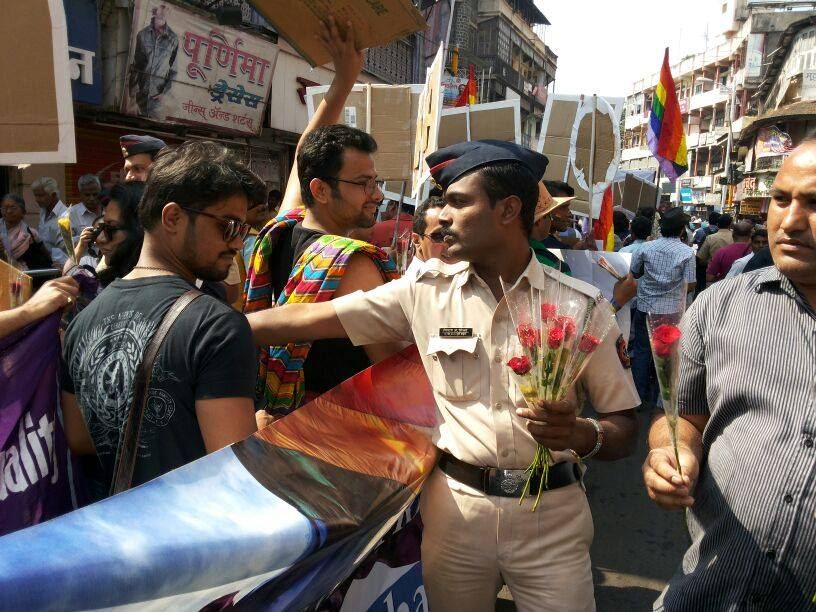A Police personnel distributing roses in Pune Pride