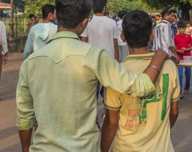 Men holding hands outside park